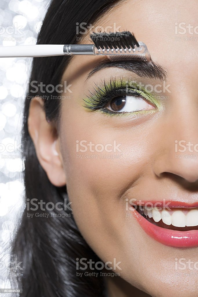 A woman brushing her eyebrow royalty-free stock photo