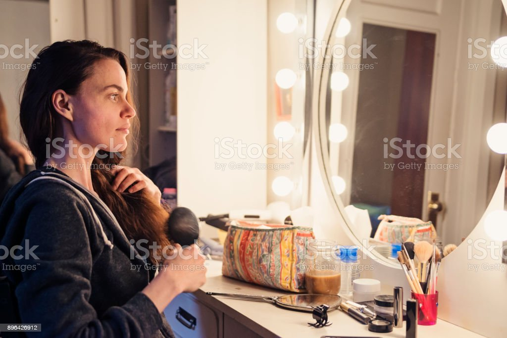 Woman brushing her hair getting ready to morning routine. stock photo