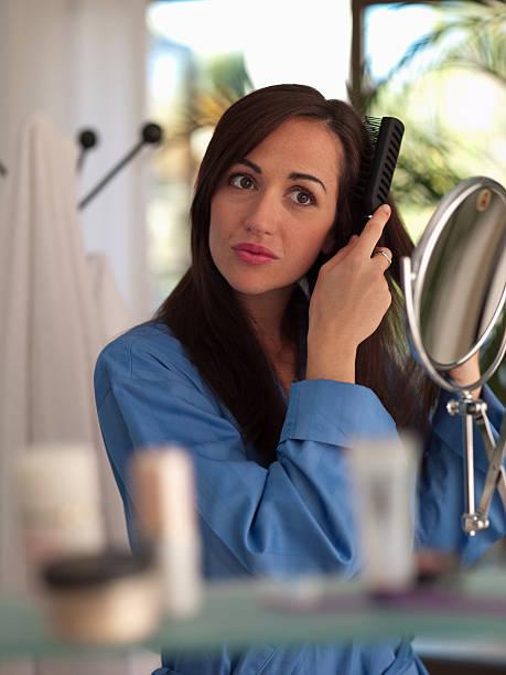 Woman brushing her hair stock photo