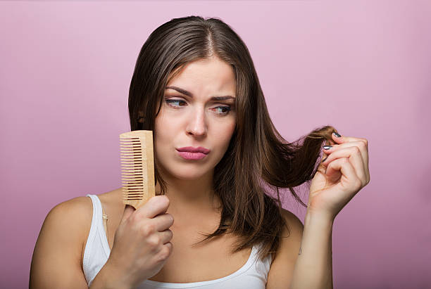 woman brushing her hair - human hair stock photos and pictures