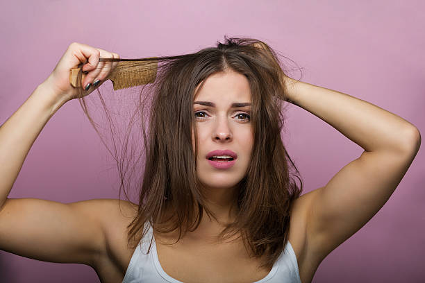 woman brushing her hair - messy hair stock photos and pictures