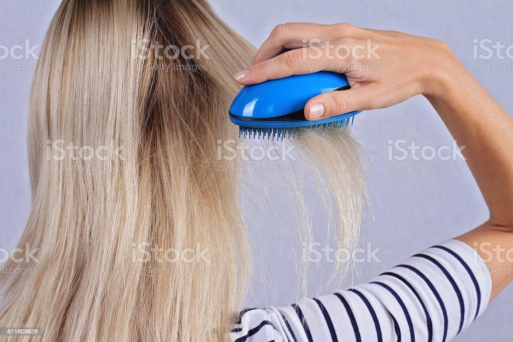 Woman brushing her hair. Thin, damaged, dry hair, split ends Woman brushing her hair. Thin, damaged, dry hair, split ends Adult Stock Photo