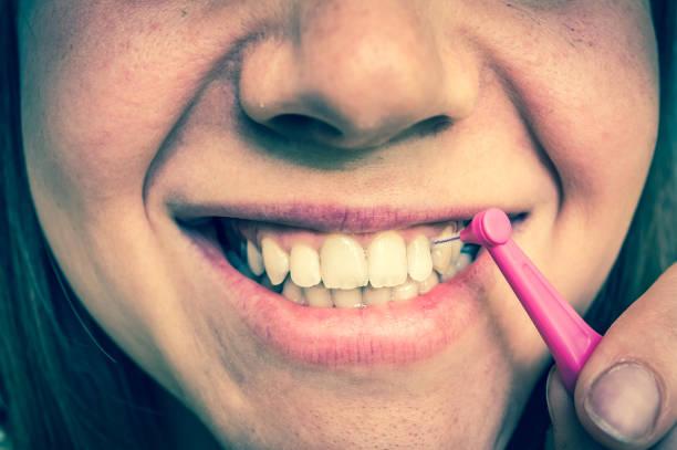 mulher escovando os dentes com escova interdental - escova interdental - fotografias e filmes do acervo