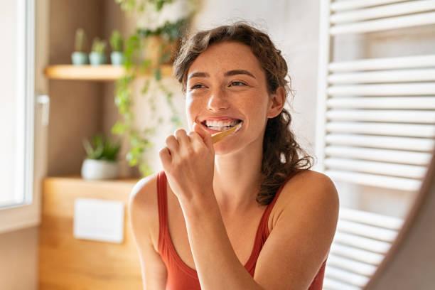 Woman brushing teeth at mirror stock photo