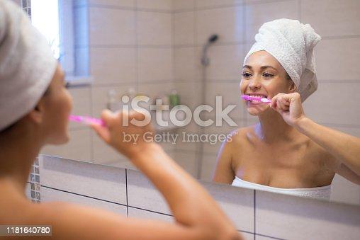 637874676istockphoto Woman brushing teeth in bathroom 1181640780
