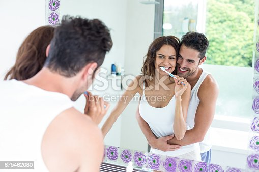 675462768 istock photo Woman brushing teeth while husband embracing her in bathroom 675462080