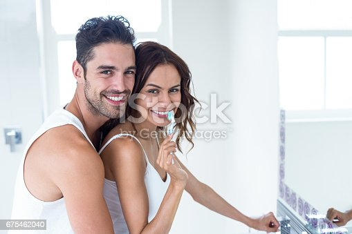 675462768 istock photo Woman brushing teeth while husband embracing her 675462040