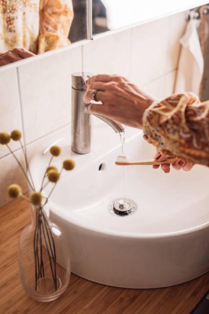 Mujer cepillarse los dientes con cepillo de dientes de madera ecológico - foto de stock