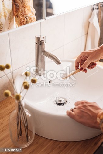Woman brushing teeth with eco friendly wooden toothbrush Candid photo taken indoors in bathroom