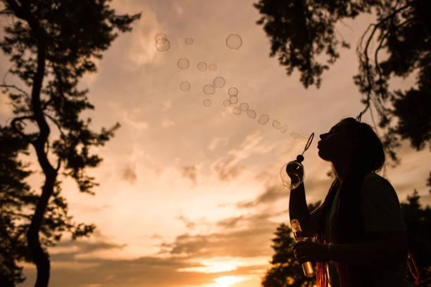 Woman bubble blowing silhouette nature concept. stock photo