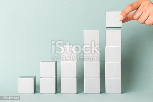 Woman building a project with wooden cubes.