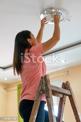 Woman Bulb replacement at home.