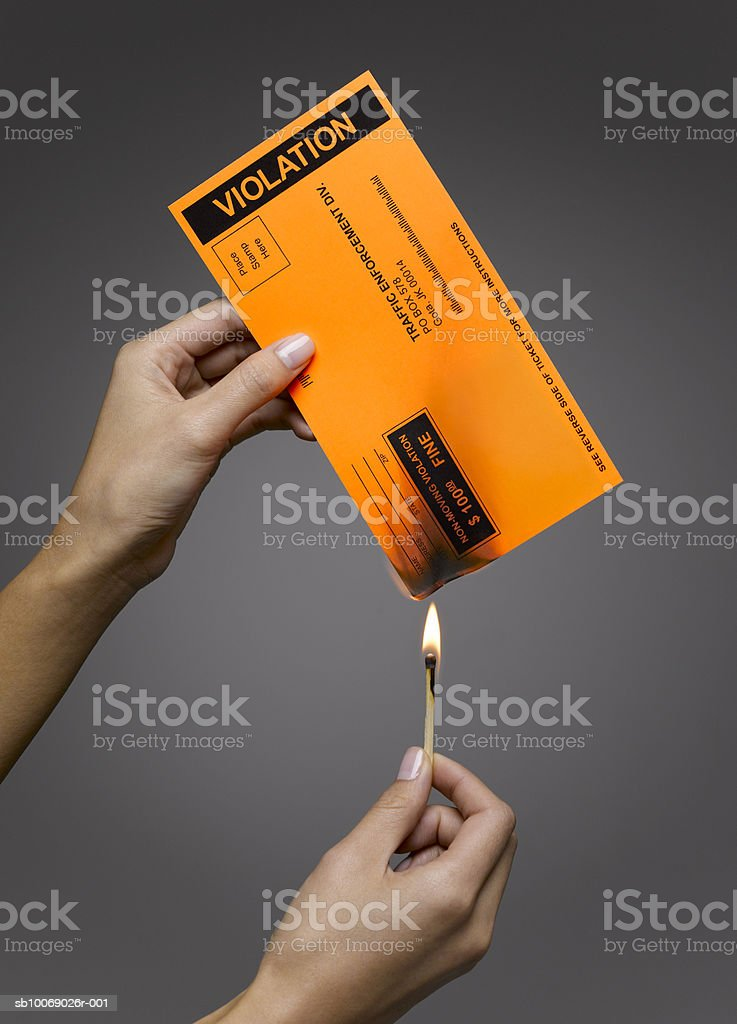 Woman burning violation ticket, close-up, studio shot royalty-free stock photo