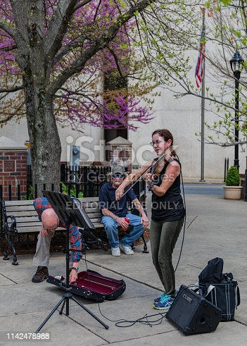 Asheville, NC, USA-4/11/19:  A woman smiling and busking in downtown, while a man puts money in her violin case, while another man sits and listens.