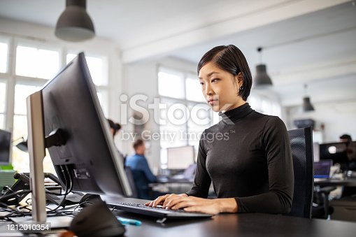 Businesswoman working on desktop computer with colleagues in background. Female executive busy working at her desk in open plan office.