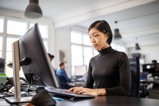 Woman busy working at her desk in open plan office stock photo