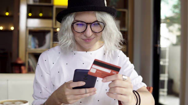 frau kaufen neue kleid online mittels smartphone und kreditkarte - brille bestellen stock-fotos und bilder