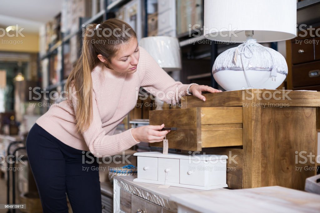 Woman buyer near chest of drawers royalty-free stock photo