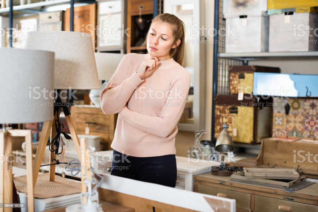 woman buyer standing in furniture shop choosing modern torchere indoors royalty-free stock photo