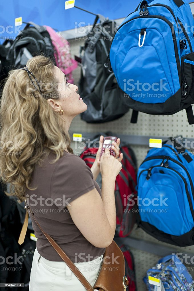 Woman buying a back pack stock photo