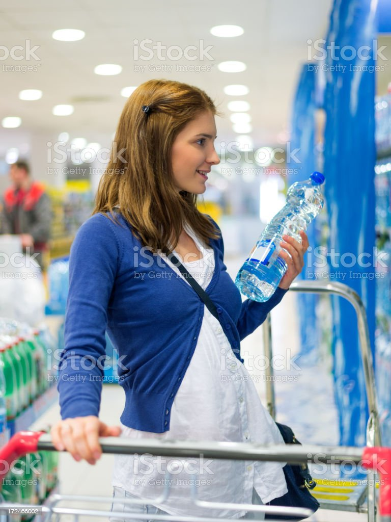 Woman buying a bottle of water in supermarket stock photo