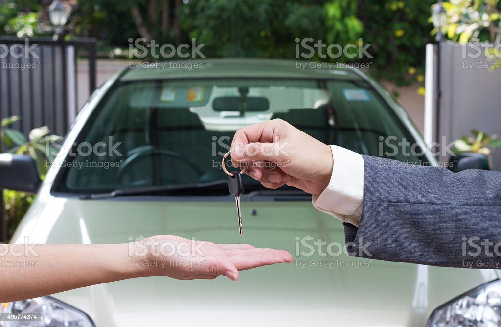 Woman buying a car and salesman handling keys stock photo
