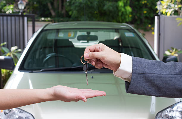 woman buying a car and salesman handling keys - used car selling stock pictures, royalty-free photos & images