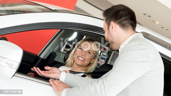 136591850 istock photo Woman buying a car in dealership sitting in her new auto 1057946786