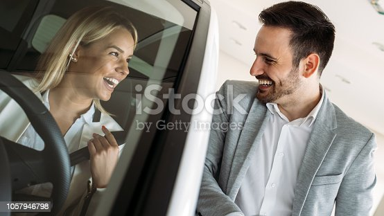 136591850 istock photo Woman buying a car in dealership sitting in her new auto 1057946798
