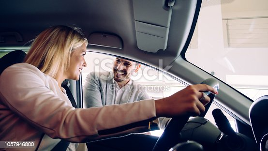 136591850 istock photo Woman buying a car in dealership sitting in her new auto 1057946800