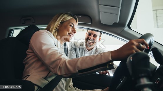 istock Woman buying a car in dealership sitting in her new auto 1137339775