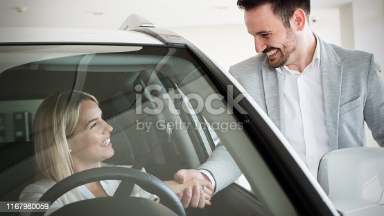 136591850 istock photo Woman buying a car in dealership sitting in her new auto 1167980059