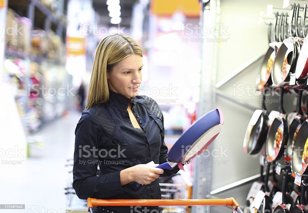 Woman buying a cooking pan. royalty-free stock photo