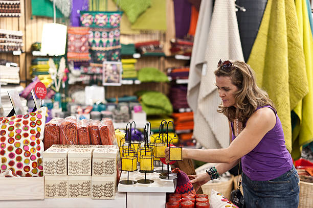 Woman buying a gift Caucasian woman buying a souvenir in a gift shop discount store stock pictures, royalty-free photos & images