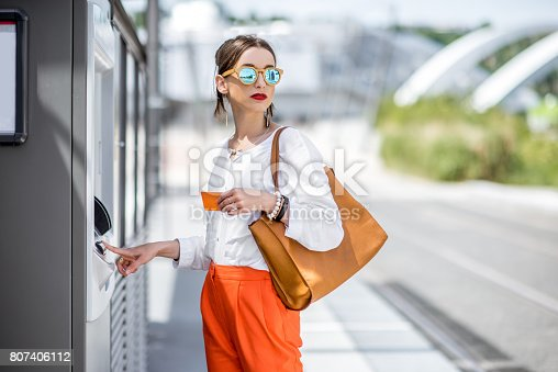 istock Woman buying a ticket or using ATM outdoors 807406112