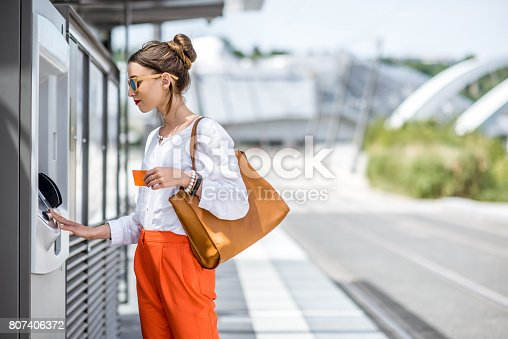 istock Woman buying a ticket or using ATM outdoors 807406372