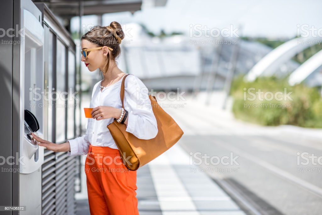 Woman buying a ticket or using ATM outdoors – zdjęcie