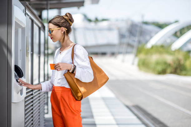 Woman buying a ticket or using ATM outdoors stock photo