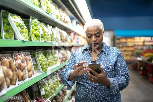 1184048369 istock photo Woman buying at supermarket using mobile phone 1221447841