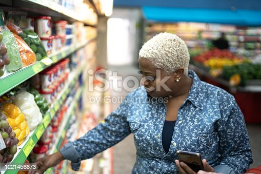 1184048369 istock photo Woman buying at supermarket using mobile phone 1221456673