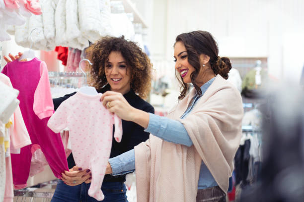 Woman buying baby sleep suit stock photo