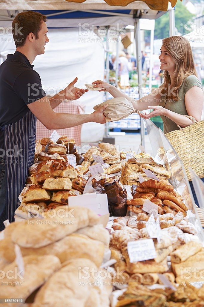Woman buying bread from market stall full of different bread stock photo