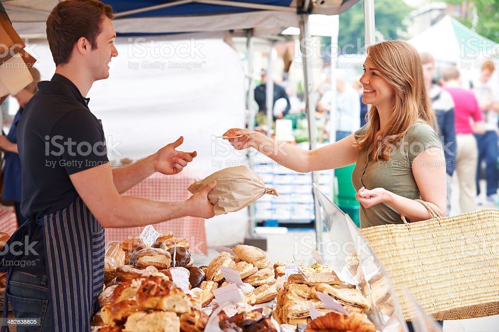 Woman Buying Bread From Market Stall royalty-free stock photo