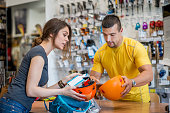 Young woman in sports store looking to buy harness and sports helmet and consulting store clerk about the quality, price etc.