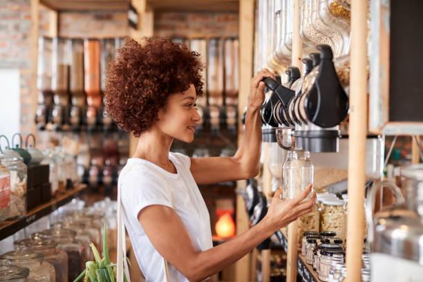 woman buying cereals and grains in sustainable plastic free grocery store - rifiuti zero foto e immagini stock