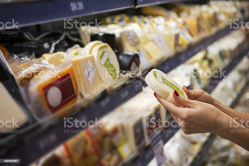 Woman buying cheese ina supermarket stock photo