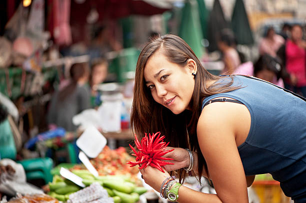 Woman Buying Chilli Peppers stock photo