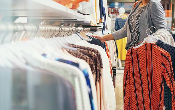 Mujer comprando ropa en la tienda. - foto de stock