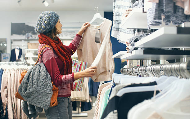 Woman buying clothes at department store. Closeup of smiling blond woman choosing clothes at department store  in local supermarket. She's holding a beige blouse and looking at it. The woman is wearing gray cap, red sweater and scarf. Side view. warm clothing stock pictures, royalty-free photos & images