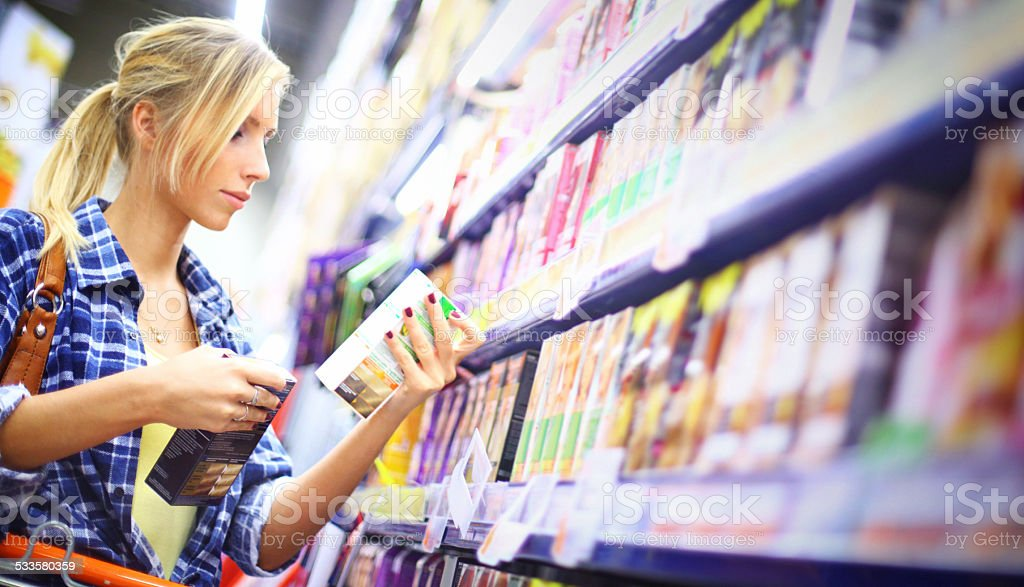 Woman buying comestics in supermarket. stock photo